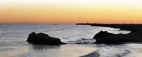 a view of the sea with sky orange in the evening