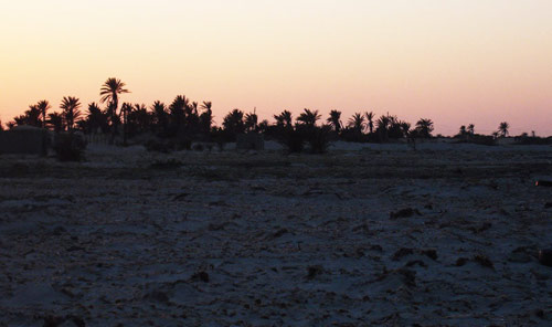 sunset by Tiboda village by the beach, showing a few mud houses and palm trees