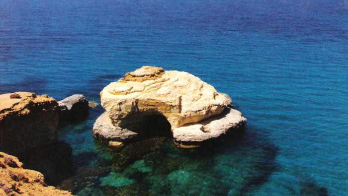 a view of a rock in the sea by the coast of alathrun