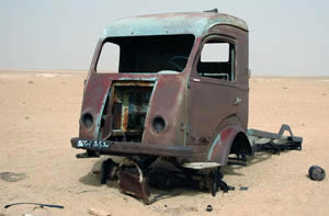 a rusty vehicle abandoned in the Hamada, sahara desert.