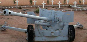 second world cannon before crossed graves in a cemetery in Tobruk