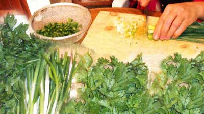 cutting the fresh herbs to be mixed with the mince