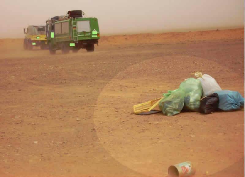 some European tourists throwing rubbish randomly in the Sahara