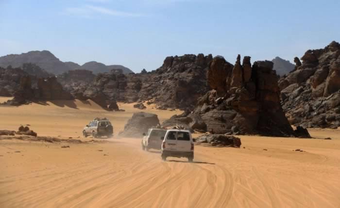 Acacus: desert cars entering an area of mountains