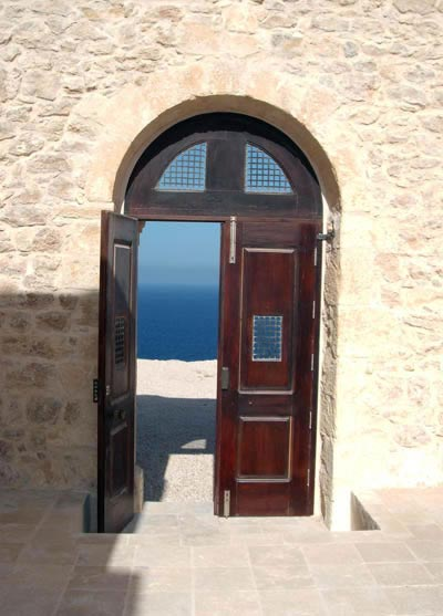 alburdi castle: a view of the sea from inside the building through the half open door.