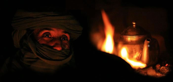 tuareg at night and a tea pot on fire in total darkness