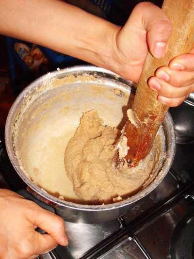 making bazin: mixing flouer in boiling water to make tough dough