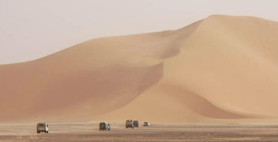 Sand mountains approached by a convoy of desert vehicles.