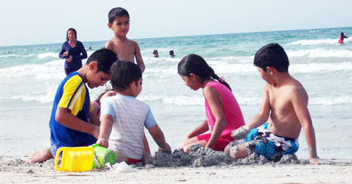 children playing with sand by the beach of Zuwarah