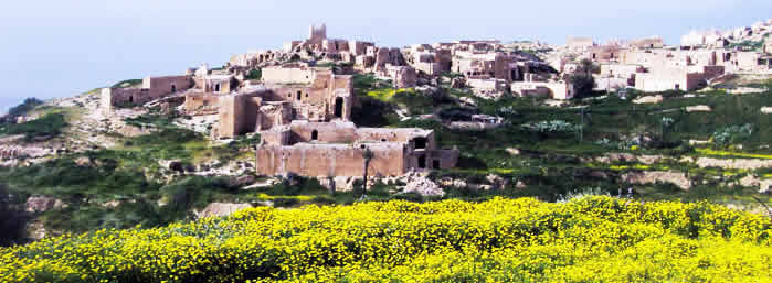 a view of Yefren with yellow flowers on hills and blue background